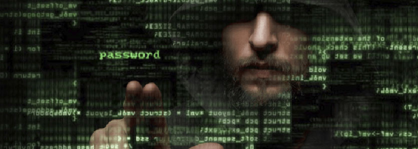 Hooded man hacking into a computer.