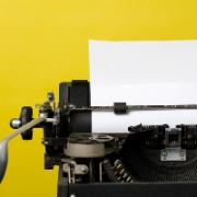 Close-up a black typewriter with a yellow background.